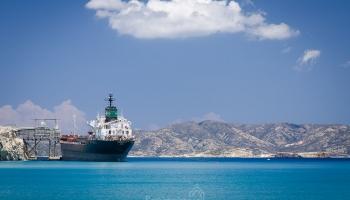 perlit cestuje přepravními pásy z nákladních aut, přes různé komíny a domy až na připravenou nákladní loď.