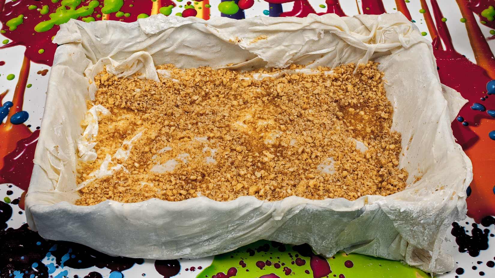 Postupně vršíme ořechovou náplň a těsto, vše prokapáváme máslem