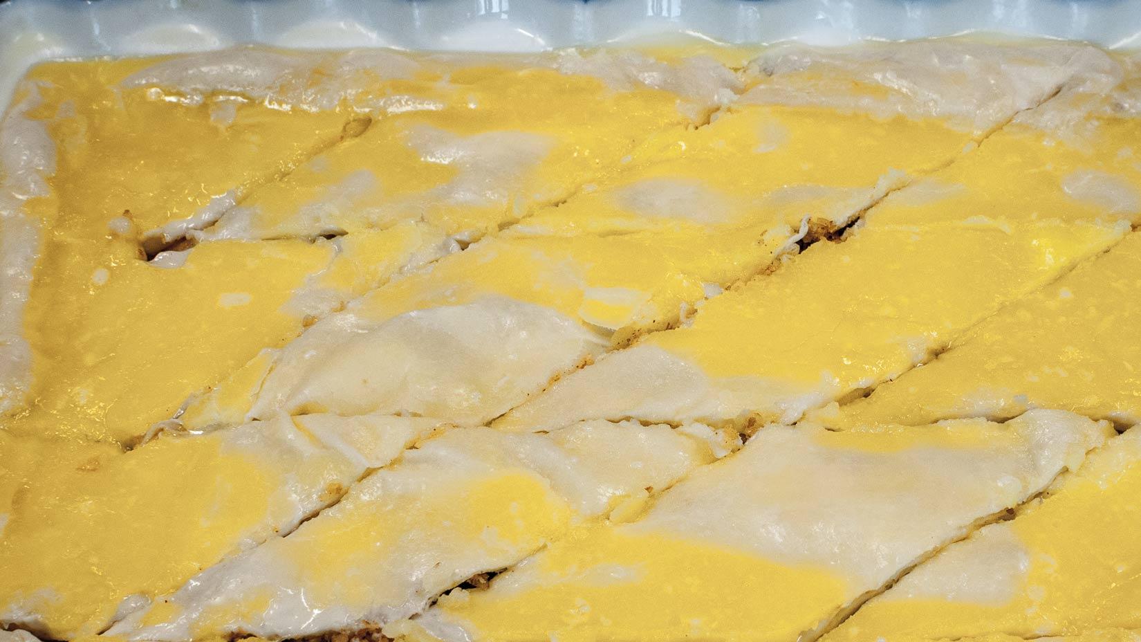 Po ztuhnutí másla baklavu rozkrájíme na budoucí porce a dáme péci