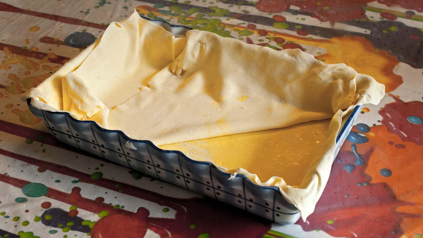Do pečící misky vymazané máslem vložte dvě vrstvy tence vyváleného lístkového těsta.
