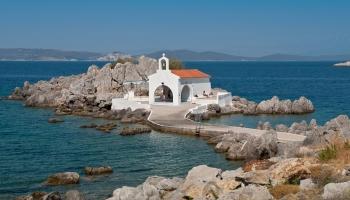 Agios Isidoros – nejkrásnější přírodní koupaliště na světě (kaplička poskytuje kýžený stín dovádějící mládeži – vše božské Bohu, lidské lidem…)