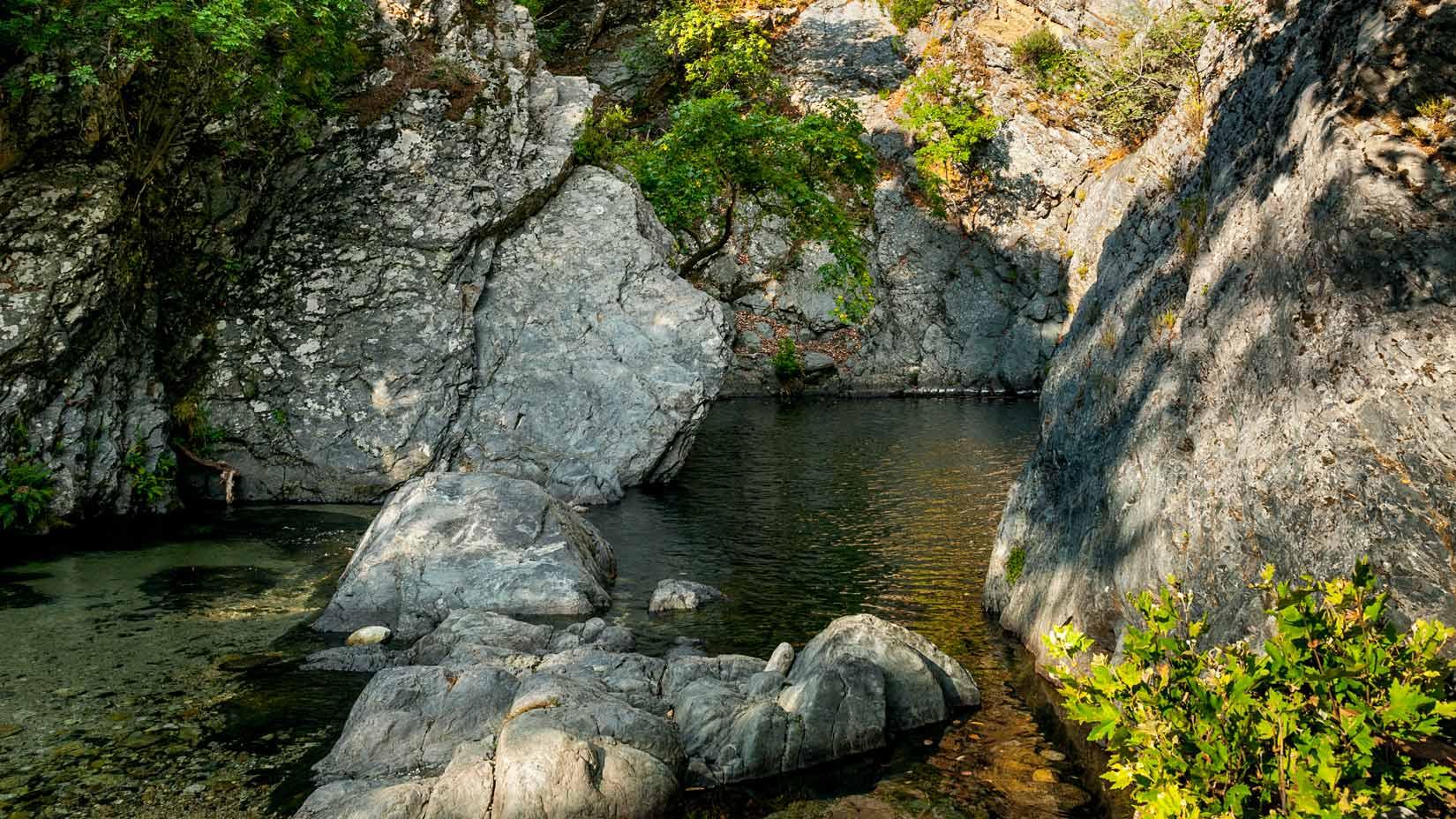 Hlubokou propadlinu mezi strmými břehy vyplňuje jezírko pod vodopádem Fonias