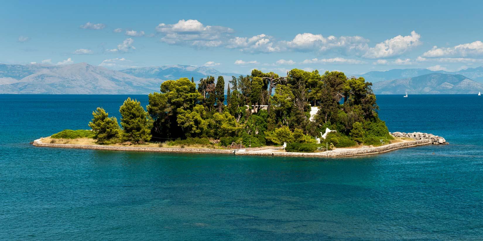Ποντικονήσι - Pontikonisi. Uvnitř zeleně, na malé vyvýšenině, se hrdě vypíná k obloze snad nejmenší klášter Řecka. Pro jednoho mnicha. Doplujte si na něj na kafíčko.