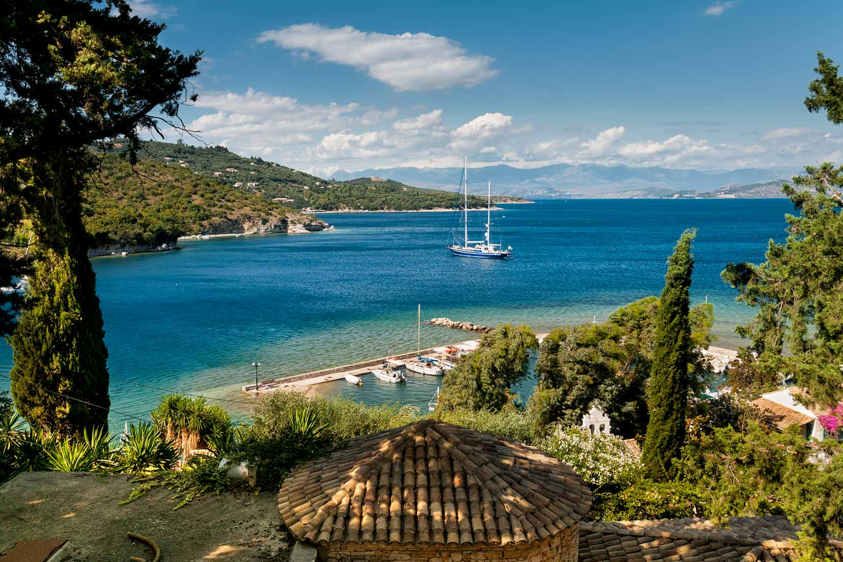 Romantický pohled na východní pobřeží Korfu přes střechy taverny Kulura