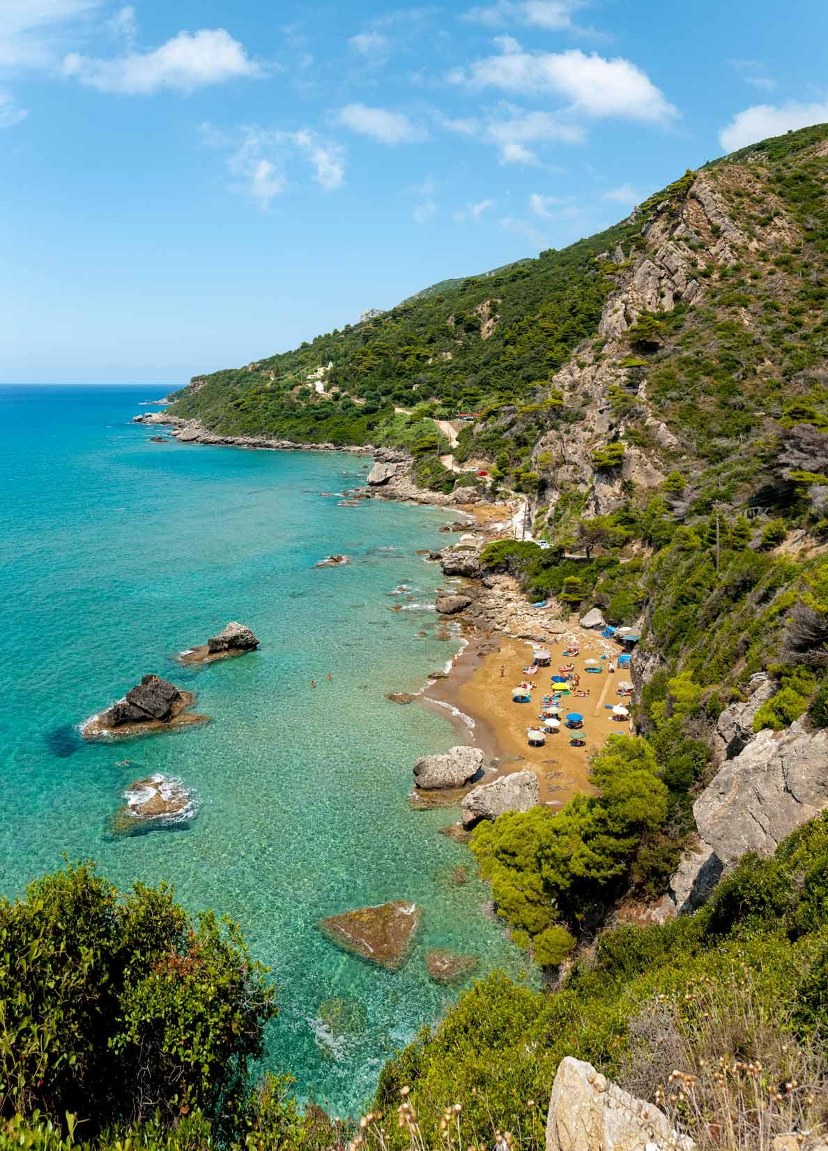Pláž Mirtiotissas po poledni. Sluníčko jemně laská holá pozadí nudistů a naturistů. I popředí...