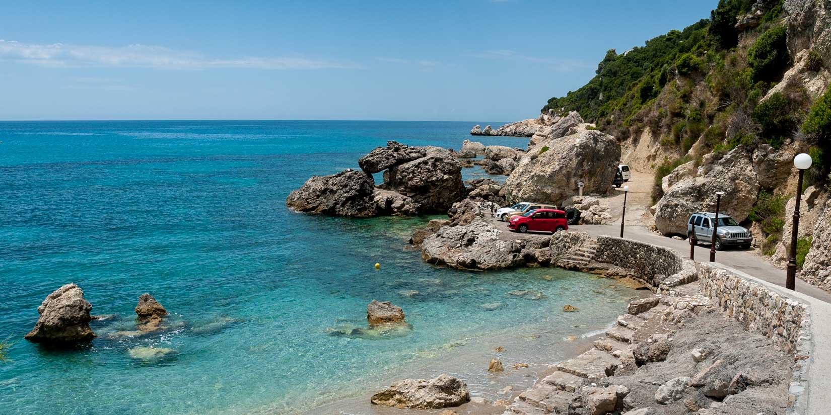 Ermones Beach, konečná, vystupovat! S typicky řeckou logikou je na začátku silnice značka Zákaz vjezdu na jednosměrnou silnici. Takže couvat!!!
