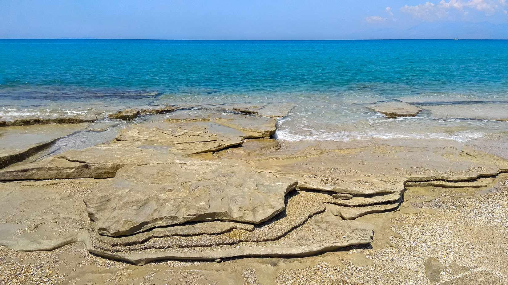 Pláž Almiros východně od Acharavi je tvořena dílem pískovcovými pláty, dílem oblázky. Krásný kus světa Korfu...