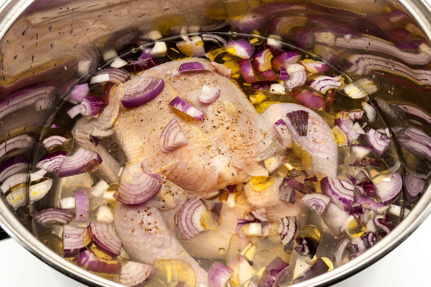 Téměř ponořené kuře obsypeme cibulí a zalijeme olivovým olejem