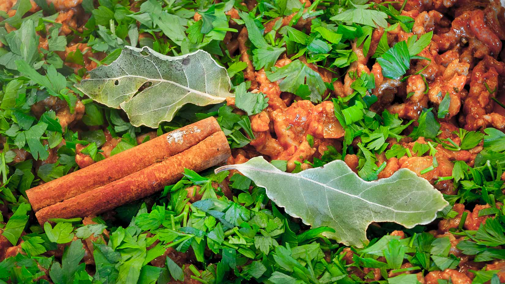 Nasekaná petrželová nať, bobkový list a skořicová kůra musaku nádherně podbarví