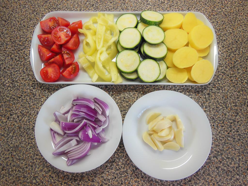 Brambory oloupeme a nakrájíme na plátky, které omyjeme a osušíme, cuketu nakrájíme také na plátky, papriku a cibuli nakrájíme na proužky, každý stroužek česneku rozkrájíme cca na 4 kousky, malá rajčátka můžeme ponechat se slupkou a rozkrojíme na poloviny nebo čtvrtiny