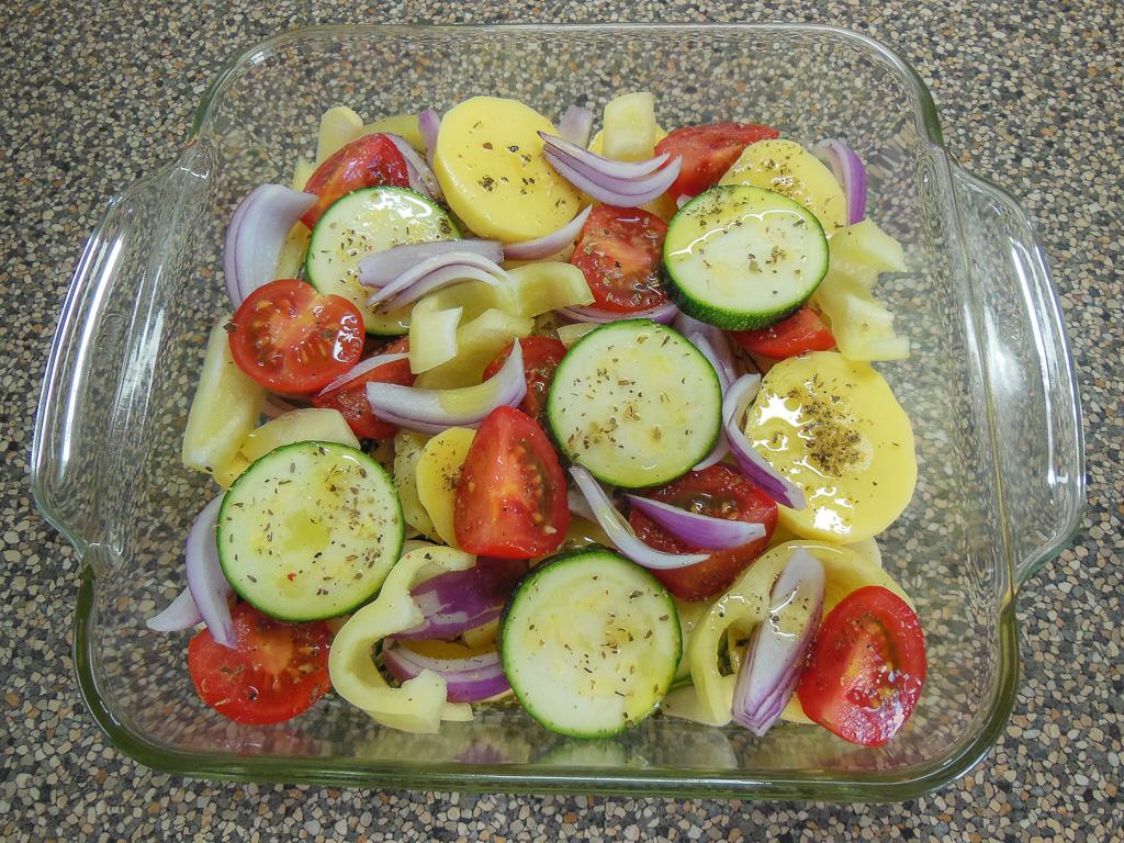 Dno zapékací misky pokapeme olivovým olejem a do misky klademe střídavě připravené brambory, cukety, papriky, rajčata a prokládáme proužky cibule a česneku
