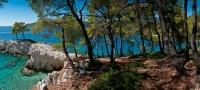 Nadýchaný koberec borovicového jehličí, omamná vůně pryskyřice (nesedat - všude pod stromy jsou kapičky čirého lepu), kontrast bílého ostrohu s modří a zelení vůkol - to je ta pravá romantika Amarantosu
