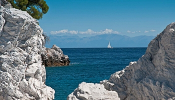 Pod Třemi borovicemi na výběžku Amarantis, na obzoru plachta bílá, za plachtou vábí Evia (Εύβοια)