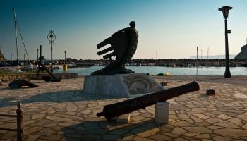 Každodenní hra světla a stínů začíná - pomník v přístavu ve Skopelosu
