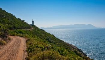 Cesta k majáku začíná kousek za Perivoli, je prašná, kamenitá, ostatně jako většina vedlejších cest na Skopelosu. Na obzoru Skiathos